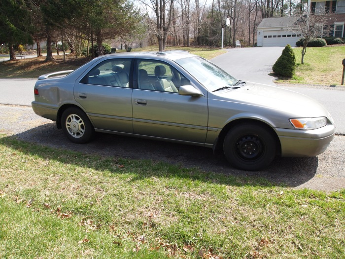 my 13-year-old Toyota Camry with missing hubcap and a fresh dent in the rear
