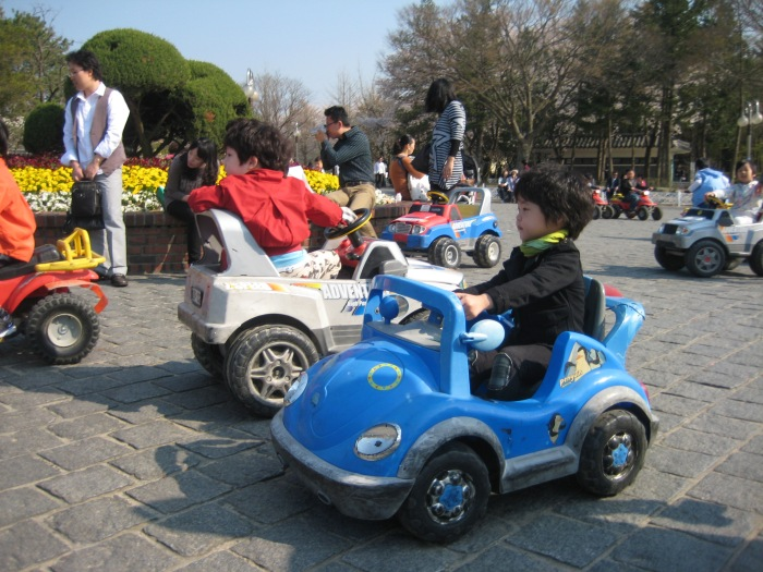 Korean children in Gyeongju, South Korea, playing in motorized cars
