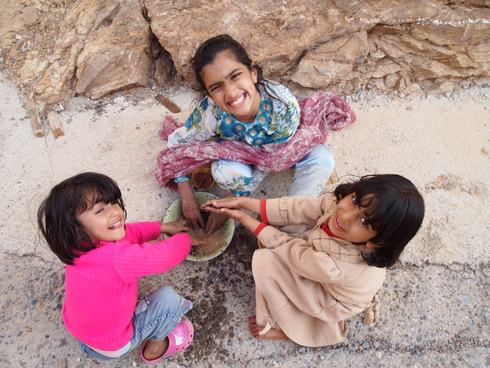 Omani girls playing in the mud on Jebel Akhdar, Oman