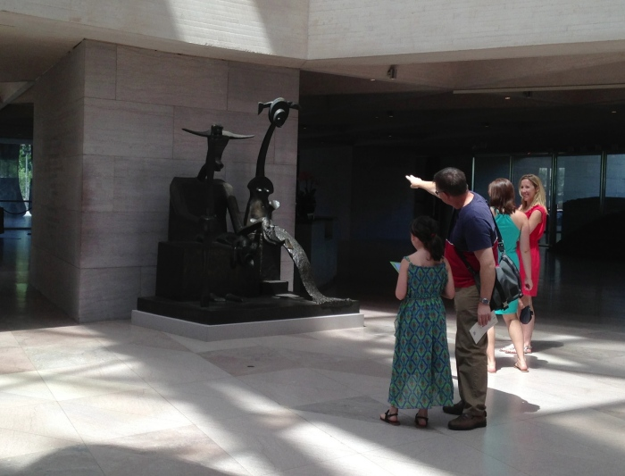 a father and daughter interacting both with each other and the sculpture
