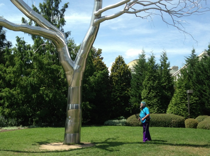 a wild looking man interacting with a metal tree at the Sculpture Garden