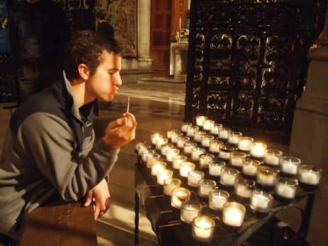 Adam lights prayer candles