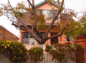 coral house with flower-bedecked fence