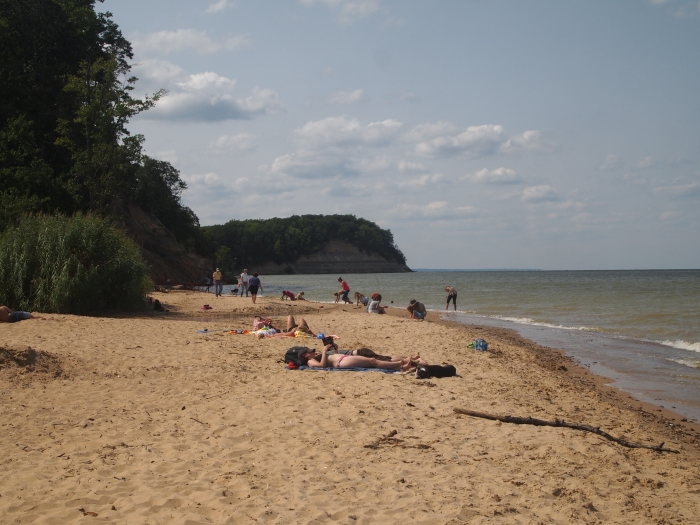 the tiny beach with the cliffs in the distance