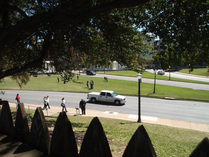 Looking through the pickets of the fence at the top of the Grassy Knoll to the assassination route