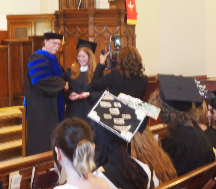 a blurry Sarah accepts her diploma