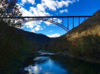 view of the New River Gorge Bridge from the small bridge below