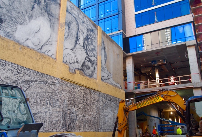 a construction zone beneath a mural in Philly